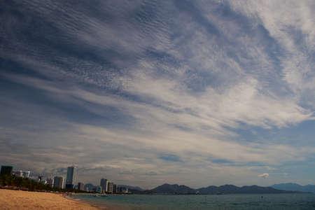 stratus: panorama of strange beautiful fleecy and stratus clouds above sea and sand beach of Vietnamese resort city