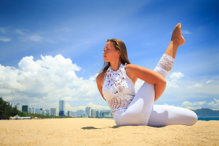 interlaced: blonde girl in white lace in yoga asana interlaced arms and leg on beach against blue sky and white clouds