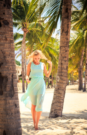 barefoot blonde: european slim blonde girl barefoot in light azure transparent frock stands with hands on head among palms on beach
