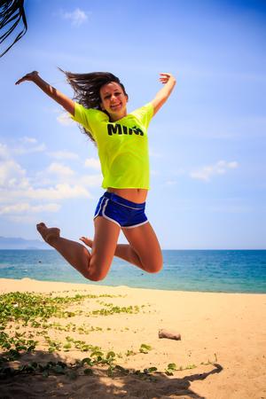 aside: european slim girl in lemon yellow t-shirt jumps with legs backward over sand beach against sea