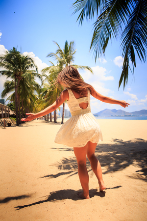 aside: european brunette slim girl in white lace frock poses with hands aside and smiles on beach against defocused city