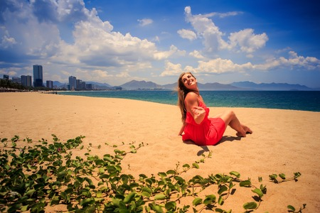 creepers: blond girl in red frock sits backside view on sand looks at sea wind shakes long hair on foreground green creepers