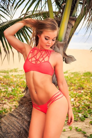 downwards: closeup cute blond longhaired slim girl in red bikini stands by palm touches hair looks downwards against palm branch
