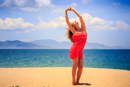 head in the sand: blond slim girl in short red frock stands on sand beach lifts hands over head against azure sea wind shakes long hair Stock Photo