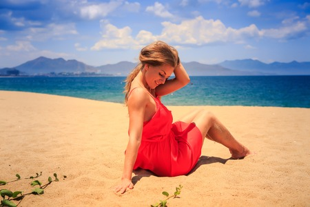 downwards: blond girl in red frock sits on sand touches hair and looks downwards against azure sea and sky Stock Photo