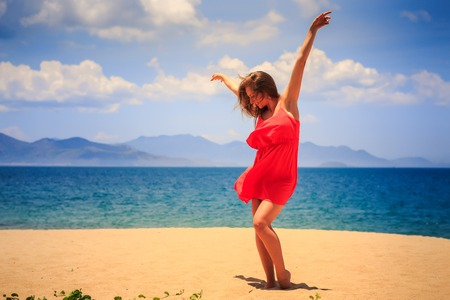 sexy girl dance: blond slim girl in short red frock dances barefoot on sand beach hands above against azure sea wind shakes long hair