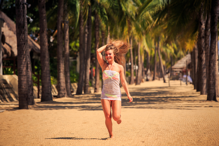 barefoot blonde: blonde slim girl in short white lace frock runs barefoot between row of palms on beach wind shakes long hair