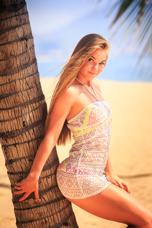 frock: blonde longhaired slim girl in short white lace frock closeup leans on palm trunk smiles and touches hair on beach