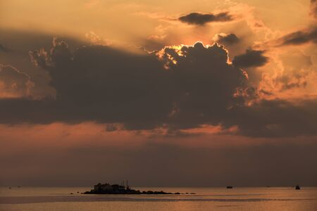 are taken: panorama of sunrise from behind golden cumulus clouds taken from embankment barrier against sea and island