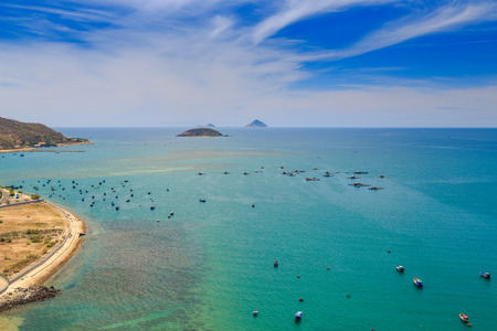 azure coast: upper panorama of fishing and tourist boats in transparent azure sea bay near coast beach against distant hilly islands