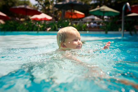 exotic gleam: closeup small blonde girl swims smiles in shallow water of hotel swimming pool against colourful shade parasols