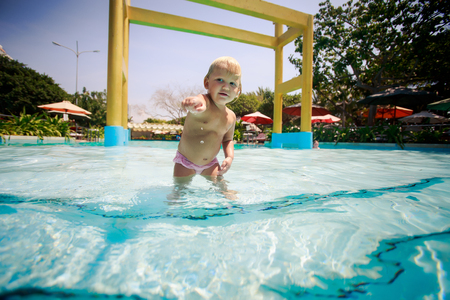 exotic gleam: small blonde girl swims with joy in shallow transparent water of hotel swimming pool against colourful parasols