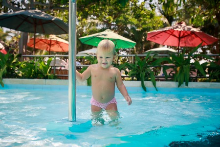 exotic gleam: small blonde girl smiles and holds pole in shallow water of hotel swimming pool against colourful shade parasols