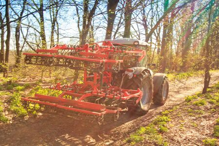 cultivator: closeup cultivator on big wheels on natural soil road against spring leafless trees and blue sky Stock Photo