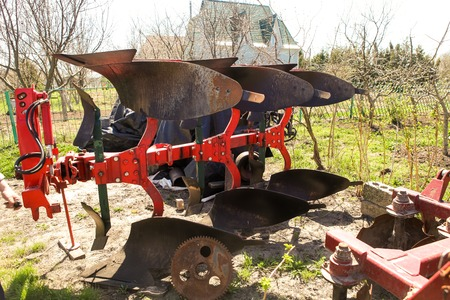 plough: large two-share tractor-drawn plough stands in country garden in spring Stock Photo