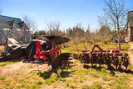 plough: large two-share tractor-drawn plough and seeding-machine stand in country garden in spring