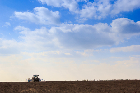 ploughed: blue sky with cumulus clouds above dark ploughed field and seeding machine in spring Stock Photo
