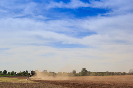 cultivator: tractor cultivator on big wheels operates on ploughed field raises great dust against spring forest and blue sky