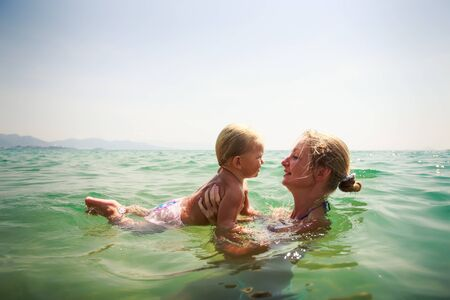 exotic gleam: closeup side-view mother teaches to swim small blonde daughter in transparent azure sea girl scares against sky