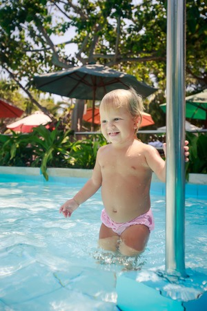metal pole: closeup small blonde girl stands and holds metal pole in shallow water of hotel pool against colourful parasols