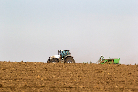 operates: distant tractor seeder on big wheels operates on horizon line against blue sky with ploughed field on foreground Stock Photo
