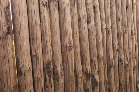 high stakes: closeup old wooden fence of logs in form of palisade in countryland