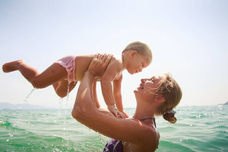 sideview: closeup side-view mother teaches to swim small blonde daughter in transparent azure sea girl scares against sky