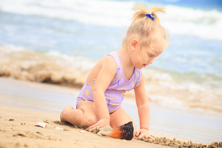 pigtail: closeup European cute little blond girl with pigtail in swimsuit sits on sand near nice shell against wave surf