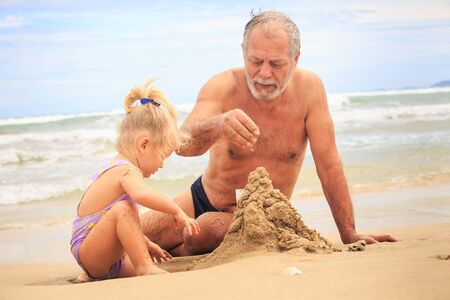 pigtail: closeup bearded grandpa little blond girl with pigtail boy in hat build sand castle on beach by wave surf