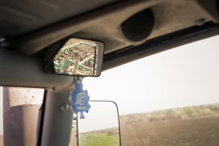 cultivator: closeup view of cultivator in upper backside mirror in tractor cabin