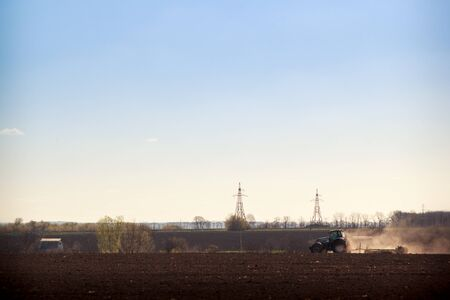 cultivator: tractor cultivator on big wheels operates on ploughed field raises dust against countryside ground road on foreground