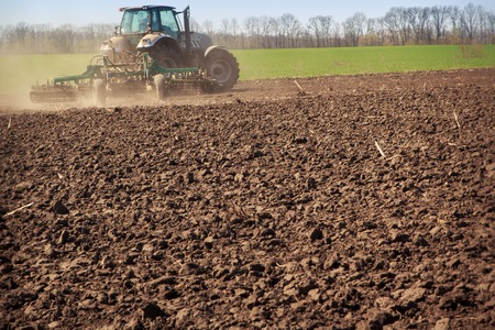 cultivator: tractor cultivator on big wheels raises great dust on ploughed ground
