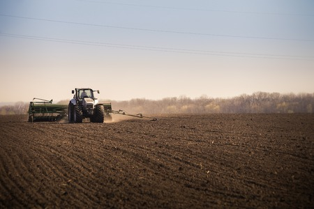 conductors: panorama of operating tractor in field at background of aerial electric conductors