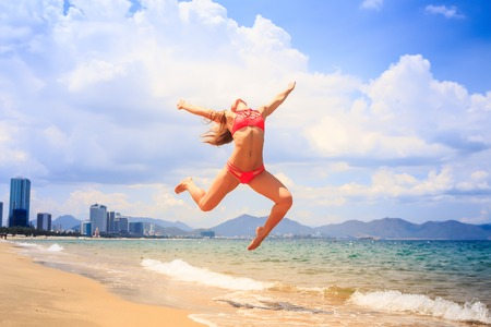 knees bent: blonde slim female gymnast in red bikini in flying jump with bent backward knees over sea edge on beach against clouds