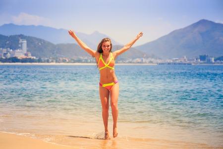 barefoot blonde: blonde longhaired slim female gymnast in bikini poses barefoot on tip toe on azure sea edge against resort city