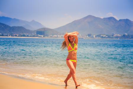 over the edge: blonde slim female gymnast in bikini poses crossing arms over head on sea edge of beach smiles against resort city