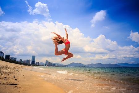 knees bent: blonde slim female gymnast in red bikini in flying jump with bent backward knees over sea edge on beach against clouds
