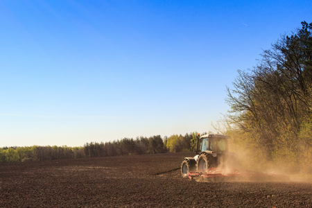 cultivator: cultivator on big wheels operates on edge of ploughed field raises dust near spring forest against blue sky