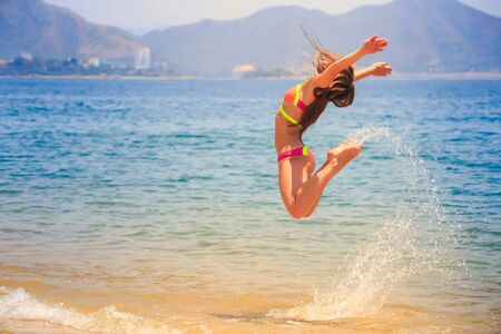 knees bent: blonde slim female gymnast in bikini side view in flying jump with bent knees over sea and splashes against hills