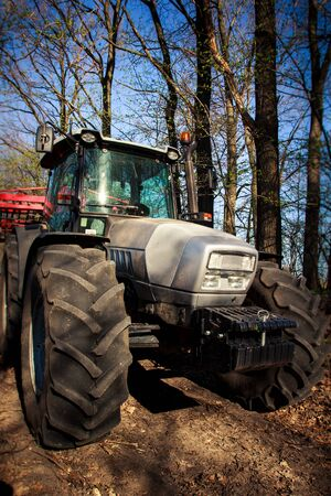 house coat: closeup side view of tractor bonnet and big wheels on natural soil road in spring forest