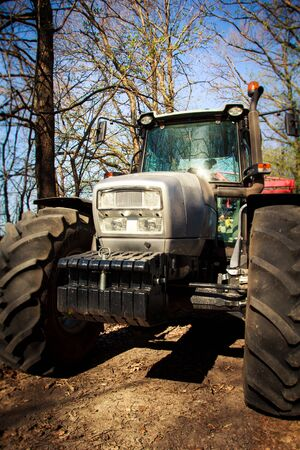house coat: closeup front view of tractor bonnet and big wheels on natural soil road in spring forest Stock Photo