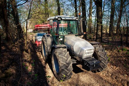 house coat: side view of tractor bonnet and big wheels on natural soil road in spring forest