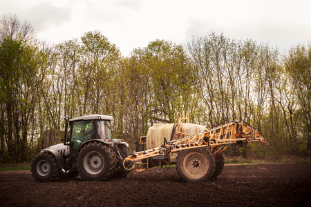 ploughed: tractor with trailer fertilizer-sprayer on ploughed field against spring trees