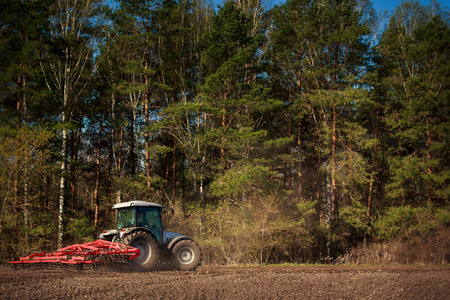 ploughed: panorama of tractor with weeding-machine on edge of ploughed field against green forest