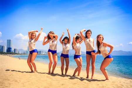 squad: squad of cheerleaders in white blue uniform stands on sand beach laughs wave hands against sea wind shakes long hair
