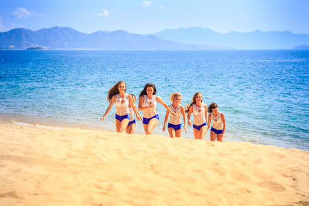 squad: squad of cute cheerleaders in white blue uniform steps out of sea and smiles on sand beach against azure sea