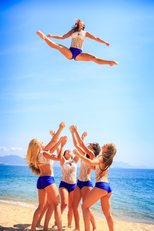 to toss: squad of cheerleaders in white blue uniform performs Toe Touch Toss on beach against azure sea wind shakes long hair Stock Photo