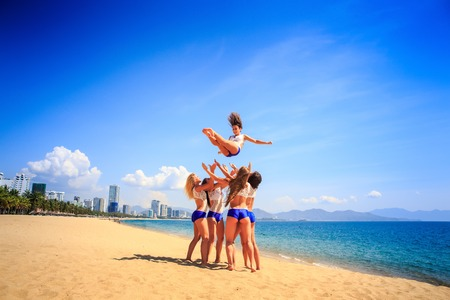 squad: squad of cheerleaders in white blue uniform performs tumbling toss on beach against azure sea wind shakes long hair