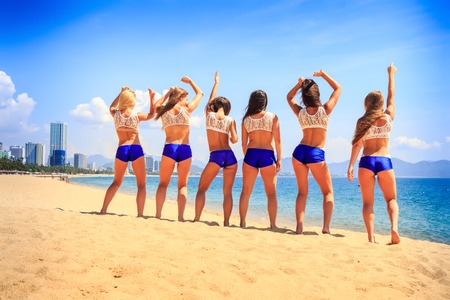 squad: squad of cheerleaders in white blue uniform stands backside view on beach wave hands against sea wind shakes long hair