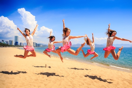 synchronously: cheerleaders in white pink uniform jump in Scales synchronously on sand beach against sea wind shakes long hair